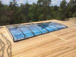 En färdigbyggd pool med poolskydd och träterrass